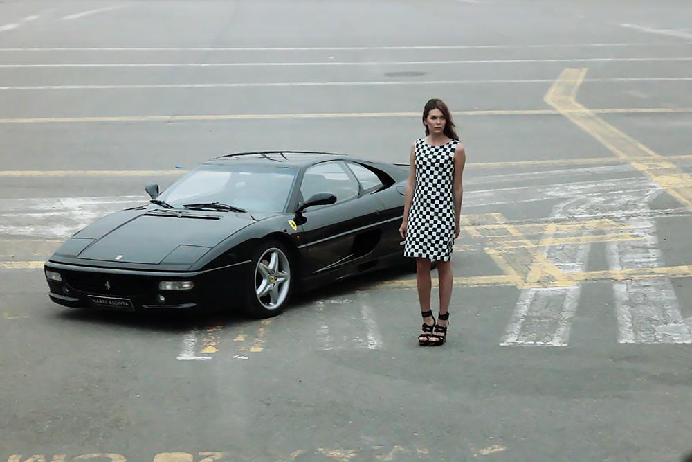 Black Ferrari F355 berlinetta with woman standing next to it